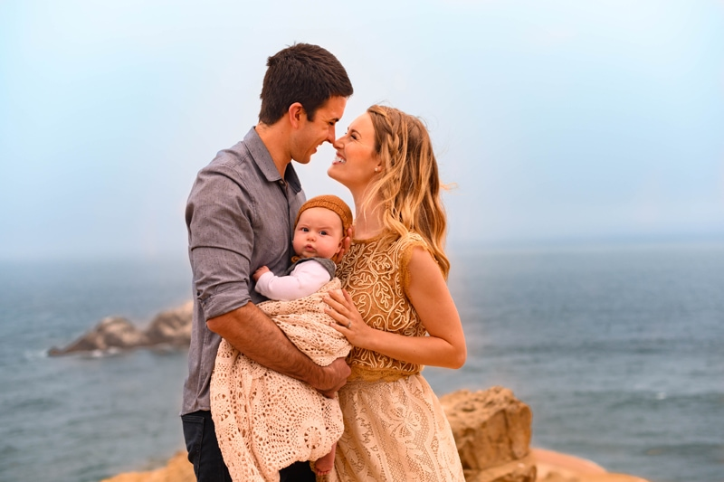Family Photography, couple holding little baby between them by the ocean